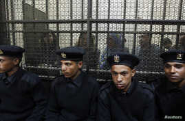 Some of the fourteen Egyptian activists who were accused of working for unlicensed non-governmental organizations (NGOs) and receiving illegal foreign funds, stand in a cage during the opening of their trial in Cairo February 26, 2012. An Egyptian co