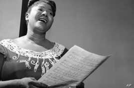 """Mahalia Jackson, """"Queen of the Gospel Singers,"""" practices a new song in her Chicago apartment, August 30, 1955."""