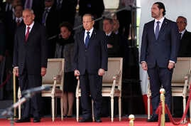 Lebanese President Michel Aoun, center, Lebanese Prime Minister Saad Hariri, and Lebanese Parliament Speaker Nabih Berri, left, attend a military parade to mark the 74th anniversary of Lebanon's independence from France in downtown Beirut, Nov. 22, 2