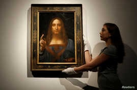 "FILE - Members of Christie's staff pose for pictures next to Leonardo da Vinci's ""Salvator Mundi"" painting which will be auctioned by Christie's in New York in November, in London, Britain, Oct. 24, 2017."