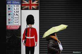 A pedestrian shelters under an umbrella as she walks past a money exchange sign in central London, Britain, Jan. 16, 2017.