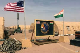 In this photo taken April 16, 2018, a U.S. and Niger flag are raised at the base camp for air forces and other personnel supporting the construction of Niger Air Base 201 in Agadez, Niger. On the edge of the Sahara Desert, the U.S. is building a base...