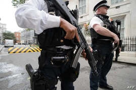 Armed police officers hold guns as they stand on Downing Street, in central London, Aug. 29, 2014.