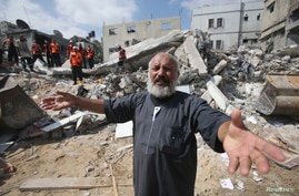 A  Palestinian man reacts as rescue workers search for victims after an airstrike in Khan Younis in the southern Gaza Strip July 29, 2014.
