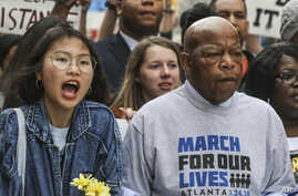 U.S. Rep. John Lewis, right, leads a march of thousands through the streets of Atlanta on March 24, 2018. Participants in Atlanta and across the nation rallied against gun violence and in support of stricter gun control.