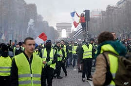 "FILE - In this Nov. 24, 2018, file photo, demonstrators, wearing ""yellow vests,"" march on the Champs-Elysees in Paris, France, as they protest the rising of the fuel prices. (AP Photo/Kamil Zihnioglu, File)"