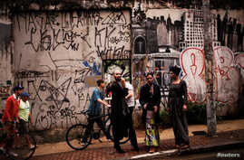 Fernanda, 20, Rodrigo, 26, and Teflon, 19, who are among members of lesbian, gay, bisexual and transgender (LGBT) community, that have been invited to live in a building that the roofless movement has occupied, stand at an entrance of the building, i