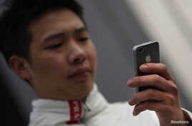 A man looks at the screen of his iPhone as he walks on a busy street in downtown Shanghai, March 13, 2013.