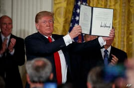 "President Donald Trump shows off a ""Space Policy Directive"" after signing it during a meeting of the National Space Council in the East Room of the White House, June 18, 2018, in Washington."