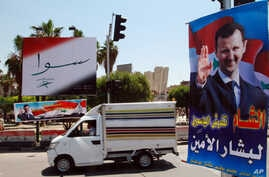 FILE - A vehicle drives past campaign posters for a presidential election in Damascus, Syria, May 12, 2014.