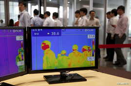 Employees walk past a thermal imaging camera at an office building in central Seoul, South Korea, June 9, 2015.