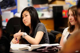 FILE - Sally Kim takes notes during a physics class at Columbia Independent School in Columbia, Mo., Feb. 27, 2012. Kim's parents, who live in South Korea, sent her to live with relatives in Columbia for a better education that provides more collegia