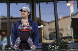 FILE - Steve Caniglia holds his six-month-old son, Boden, in San Francisco, California, Feb. 19, 2014.