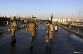 Afghan security forces walk at the site of a suicide attack in Kabul, Afghanistan, Feb. 27, 2016.
