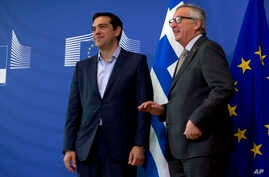 European Commission President Jean-Claude Juncker, right, speaks with Greek Prime Minister Alexis Tsipras as they arrive for a meeting at EU headquarters in Brussels, Belgium, June 3, 2015.