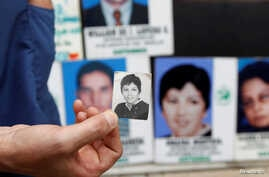 FILE - A nephew of missing person Omaira Montoya, a member of Colombia's rebel group National Liberation Army (ELN) who disappeared in 1977, holds a photograph of her during an event marking the International Day of the Victims of Enforced Disappeara