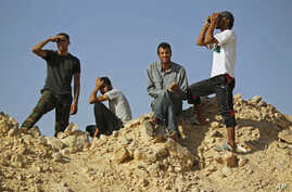 Libyan rebel fighters watch the border at the frontline of Al-Qawalish in the western mountains of Libya, after a battle with forces loyal to Libyan leader Moammar Gadhafi, July 14, 2011
