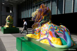 "FILE - ""Stephen"" (L) and ""Stitt"", the two lions in rainbow colors to show support for the LGBT (lesbian, gay, bisexual and transgender) community, are newly displayed at HSBC's main branch in Hong Kong, Dec. 7, 2016."