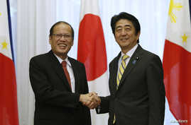 Philippines' President Benigno Aquino shakes hands with Japan's Prime Minister Shinzo Abe (R) at the start of their meeting at the prime minister's official residence in Tokyo, June 24, 2014.