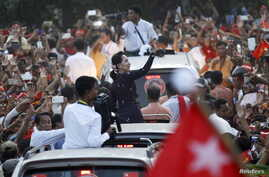 Myanmar pro-democracy leader Aung San Suu Kyi greets supporters while arriving at a campaign rally ahead of upcoming general elections in Yangon, Nov.1, 2015.