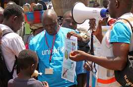 Health workers teach people about the Ebola virus and how to prevent infection, in Conakry, Guinea, Monday, March 31, 2014.   (AP Photo/ Youssouf Bah)