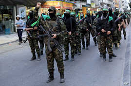 FILE - Palestinian masked militants of Izzedine al-Qassam Brigades, a military wing of Hamas, mark the 11th anniversary of the Israeli assassination of Hamas spiritual leader Sheikh Ahmad Yassin in Gaza, in the northern Gaza Strip.
