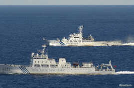 An aerial photo from a Kyodo News aircraft shows the Chinese marine surveillance ship Haijian No. 51 (front) cruising as a Japan Coast Guard ship sails near the disputed islands, called Senkaku in Japan and Diaoyu in China, in the East China Sea, Sep