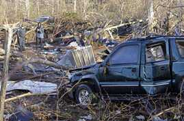 A vehicle sits among debris in an area near Linden, Tenn., Dec. 24, 2015. Several people were killed in Mississippi, Tennessee and Arkansas as spring-like storms mixed with unseasonably warm weather spawned rare Christmastime tornadoes in the South.
