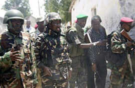 Somali president Sheik Sharif Sheik Ahmed (2nd L) comes to see where police displayed the bodies of four al-Shabab fighters killed during fighting in Mogadishu, Mar 22 2011