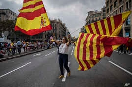 """A woman waves flags of Catalonia and Spain as people celebrate a holiday known as """"Dia de la Hispanidad"""" or Spain's National Day in Barcelona, Spain, Oct. 12, 2017."""