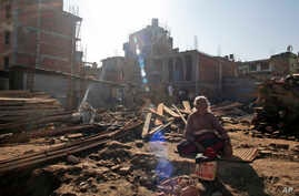 Mohan Keshari Hyanhaju, 80, sunbathes at the spot where her house stood before it was destroyed by the 2015 earthquake in Bhaktapur, Nepal, Jan. 4, 2017. People who lost their homes in the devastating earthquake that hit Nepal nearly two years ago a