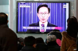 People watch a television airing a live broadcast of South Korean President Lee Myung-bak's retirement speech at Seoul Railway Station in Seoul, South Korea, February 19, 2013.