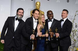 """Anthony Katagas, from left, Jeremy Kleiner, Dede Gardner, Steve McQueen, and Brad Pitt pose in the press room with the award for best picture of the year for """"12 Years a Slave"""" during the Oscars."""