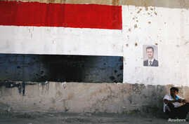 A man sits near a poster of Syrian President Bashar al Assad during the re-opening of the road between Homs and Hama in Talbisi, Syria June 6, 2018.