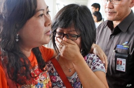 A relative of AirAsia flight QZ8501 passengers weeps as she waits for the latest news on the missing jetliner at Juanda International Airport in Surabaya, East Java, Indonesia, Dec. 28, 2014.