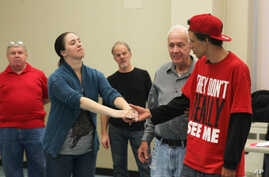 """Army veteran Carissa DiPietro takes the hand of Iraq war veteran Mike Mitchels while rehearsing for """"Julius Caesar"""" in Milwaukee. A group of actors is using William Shakespeare's plays to help veterans with emotional and addiction issues heal, Sept."""