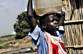 A Sudanese boy carries water home for his family.