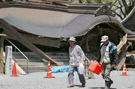 Evacuees walk past the historic Aso Shrine collapsed by powerful earthquakes in Aso, Kumamoto prefecture,  Japan, April 17, 2016.