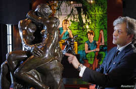 """Auctioneer Alexandre Giquello looks at the sculpture """"Le Baiser"""" (""""The Kiss""""), bronze cast made in 1927, which is part of an exceptional sale of five remarkable bronzes by the French sculptor Auguste Rodin, displayed in Paris, Feb. 11, 2016."""