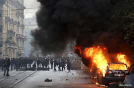 A car burns as protesters are seen during a rally against Expo 2015 in Milan, Italy, May 1, 2015.