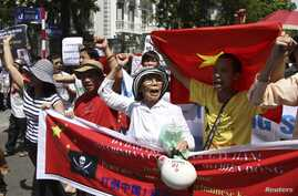 Protesters hold banners while chanting slogans during an anti-China protest along a street in Hanoi, July 22, 2012.