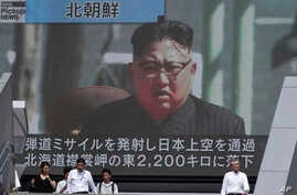 People walk past a public TV screen showing a file footage of North Korean leader Kim Jong Un during news on North's missile launch, in Tokyo, Sept. 15, 2017. North Korea fired an intermediate-range missile over Japan into the northern Pacific Ocean ...