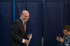 Romania PresidentTraian Basescu heads to cast his vote, as a young man takes pictures with his mobile phone, in Bucharest, Romania, Nov. 2, 2014.