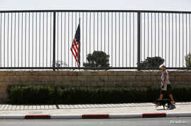 FILE - A woman walks with a dog past the U.S. consulate in Jerusalem, Aug. 4, 2013.