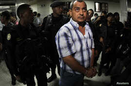 FILE - Suspect Elio Lorenzana is escorted by police officers in the Supreme Court in Guatemala City, Guatemala, Nov. 8, 2011.