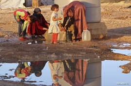 Syrian refugees collect water at Al Zaatri refugee camp near the border with Syria, in the Jordanian city of Mafraq, Sept, 26, 2013.