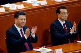 Chinese President Xi Jinping, left, and Chinese Premier Li Keqiang applaud during the opening session of the annual National People's Congress at the Great Hall of the People in Beijing, March 5, 2018.