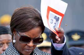 FILE - A bee hovers near Zimbabwe's first lady Grace Mugabe's head, as an aide comes to her assistance, during a funeral service in Harare, May, 13, 2017. Mugabe faces charges of assault after an incident at a plush Johannesburg, South Africa, hotel.