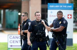 Police guard the emergency room entrance of Our Lady Of The Lake Medical Center, where wounded officers were brought, in Baton Rouge, La., July 17, 2016.
