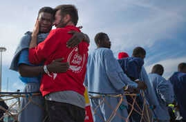 Kybumba Fran, 25, from Cameroon, cries with the head of the mission of Proactive Open Arms NGO Riccardo Gatti, from Italy, as he leaves the Golfo Azzurro rescue vessel after arriving at the port of Pozzallo, south of Sicily, Italy, with more than 220